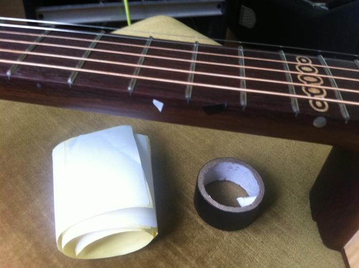 "Using white sticky paper and black tape to temporarily  ""correct' the 10th fret marker"