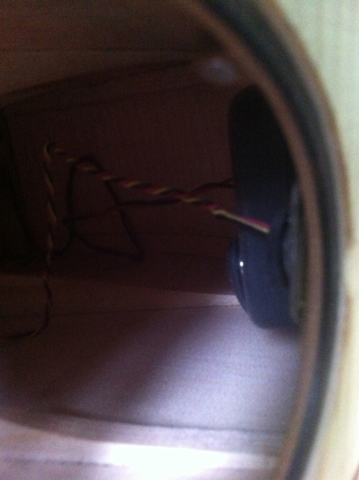 Looking into the soundhole at the volume control and battery pouch beyond